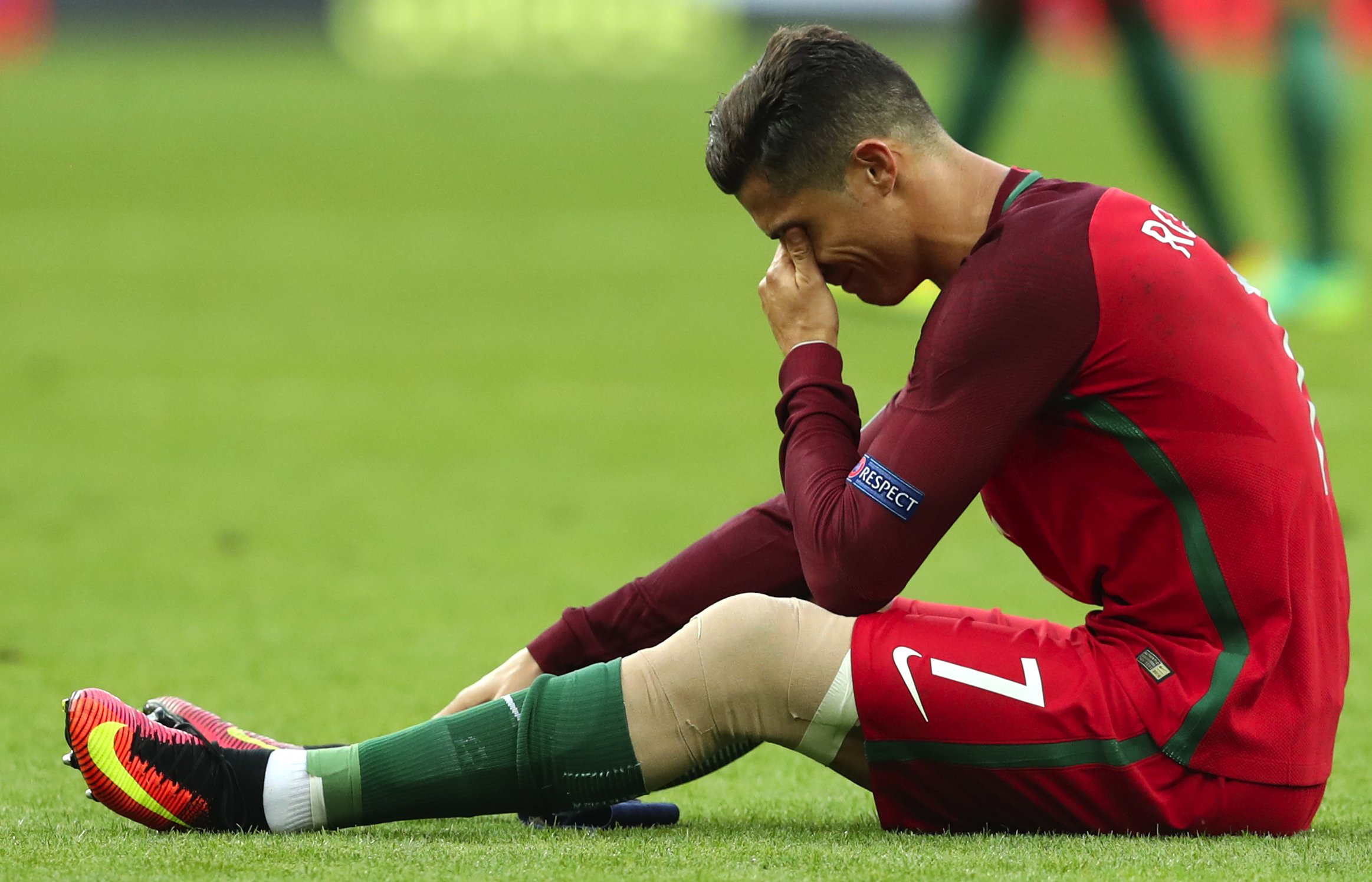 Portugal's Cristiano Ronaldo cries on the pitch during the Euro 2016 final soccer match between Portugal and France at the Stade de France in Saint-Denis, north of Paris, Sunday, July 10, 2016. (AP Photo/Thanassis Stavrakis)