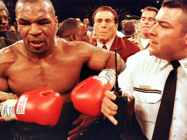 LAS VEGAS, UNITED STATES: Mike Tyson (L) is held back by police after his fight against Evander Holyfield 28 June for the WBA heavyweight champioship at the MGM Grand Garden Arena in Las Vegas, NV. Holyfield won on a disqualifiation at the end of the third round after Tyson bit Holyfield's ears. AFP PHOTO/JEFF HAYNES (Photo credit should read JEFF HAYNES/AFP/Getty Images)