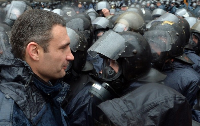 One of the leaders of the pro-European Ukrainian opposition Vitaliy Klitschko (L) faces riot police surrounding the Ukrainian Cabinet of the Ministers during a protest in Kiev on November 25, 2013. Pro-West Ukrainians staged the biggest protest rally in Kiev since the 2004 Orange Revolution, demanding that the government sign a key pact with the European Union. The opposition called the rally after President Viktor Yanukovych's government reversed a plan to sign a historic deal deepening ties with the European Union, in a U-turn critics said was forced by the Kremlin. AFP PHOTO/ SERGEI SUPINSKY
